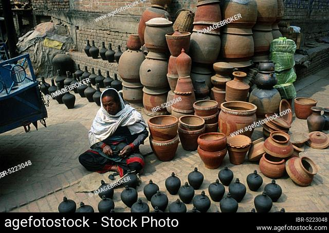 Woman processing earthenware jugs at the Pottery market, Potters' Square, Potters' Square, Bhaktapur, Nepal, Asia