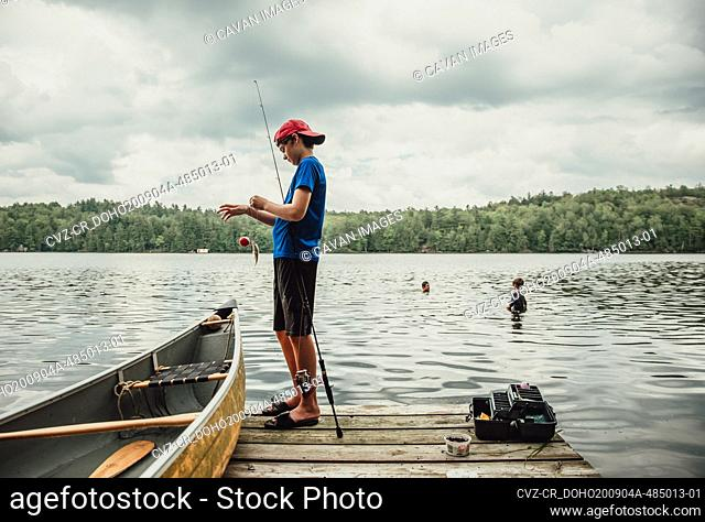 Teen boy fishing from a dock on a lake with brothers swimming nearby