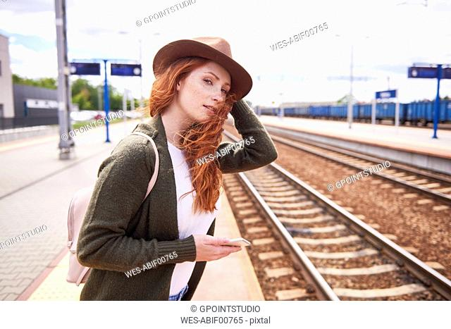 Portrait of redheaded woman with hat standing at platform
