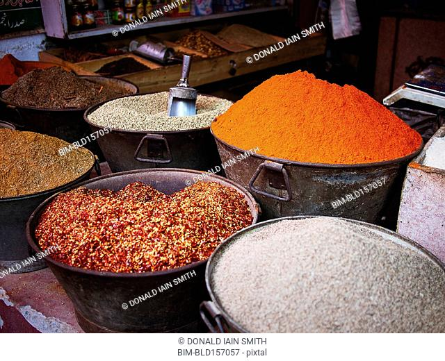 Buckets of dried spices for sale in market