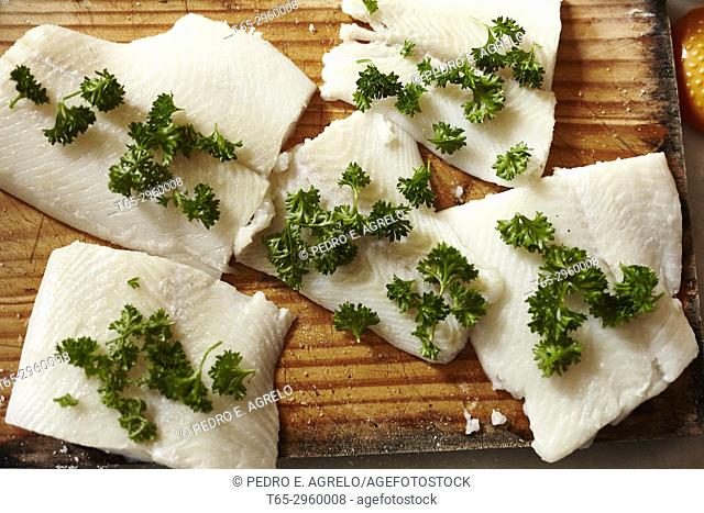 Fletan fillets, seasoned with parsley and salt on a wooden board