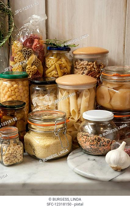 Still life arrangement in a pantry of storage jars of past, nuts, jams, olives, fruit and lentils, in a pantry on a marble shelf