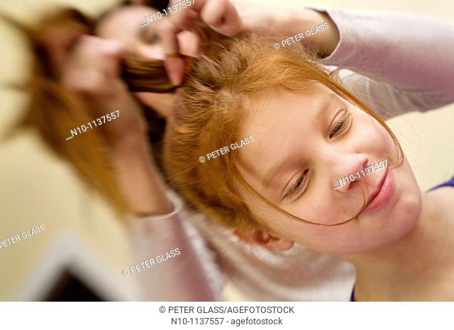 Mother adjusting the hair of her preteen redhead daughter