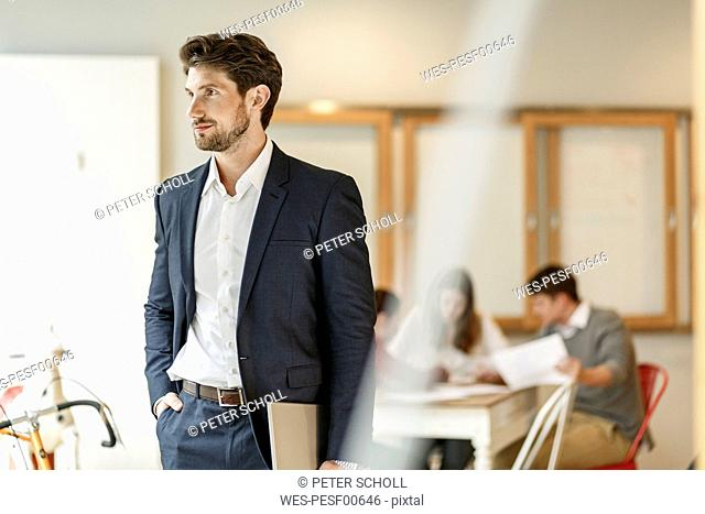 Businessman holding tablet with a meeting in background