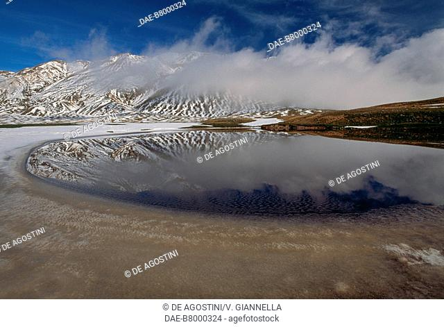View of the snow-covered slopes of Mount Prena (2561 m) surrounded by low clouds from the Pietranzoni Lake, Campo Imperatore