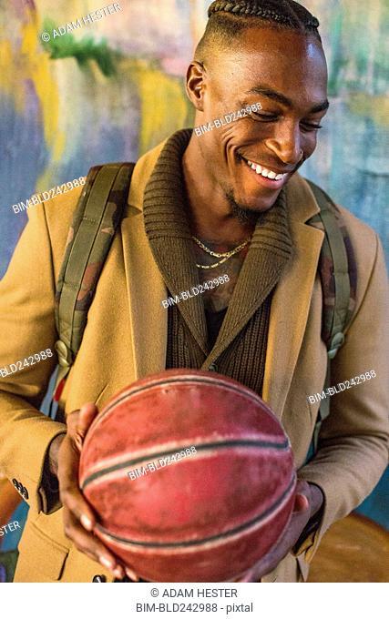 Laughing Black man wearing backpack holding basketball