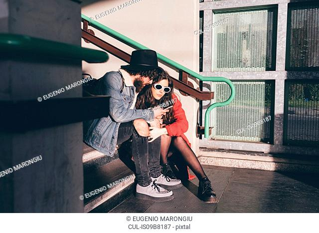 Young couple sitting on steps, looking at smartphone