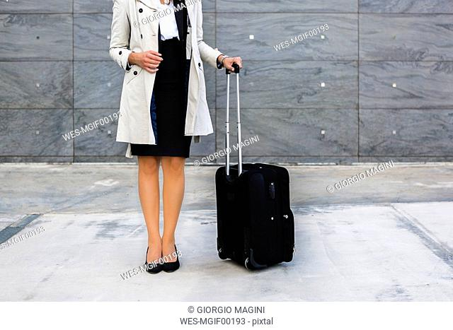 Businesswoman with suitcase wearing trench coat, partial view