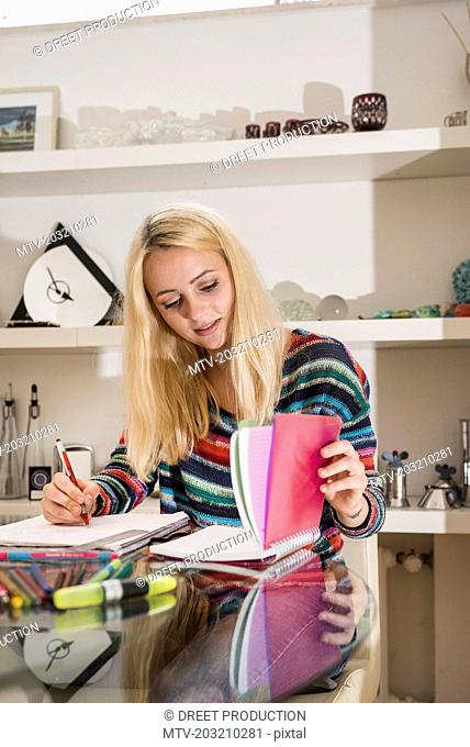 Young student doing homework in the living room, Bavaria, Germany