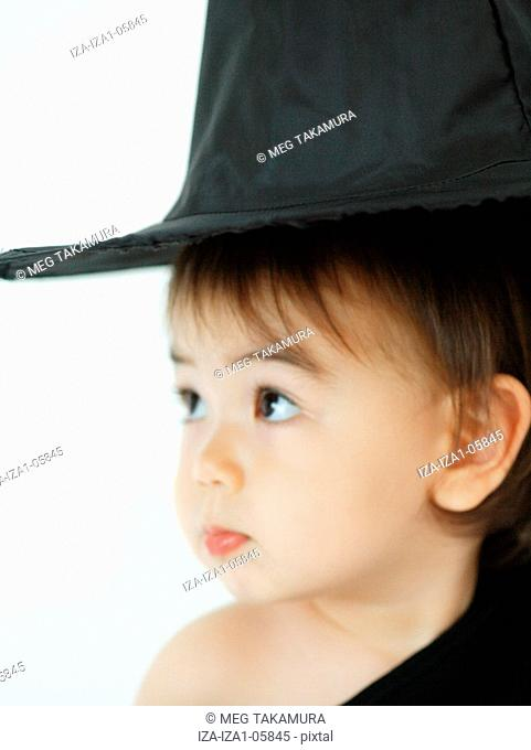 Close-up of a baby girl wearing a witch's hat