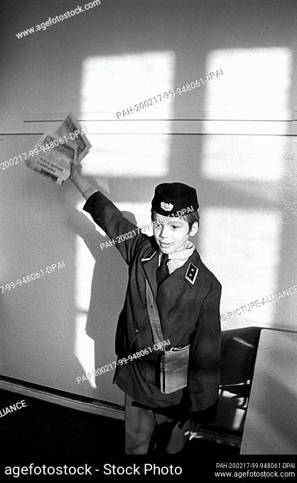 """01 January 1979, Saxony, Leipzig: A child in a GDR postal uniform shows editions of the company newspaper """"""""Der Bauarbeiter"""""""" at the end of the seventies"""