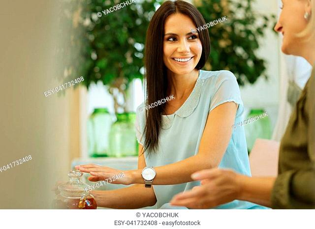 Family day. Joyful young woman smiling to her mother while pouring tea