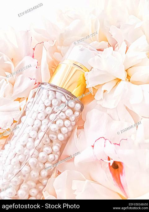Luxurious cosmetic bottle as antiaging skincare product on background of flowers, blank label packaging for body care branding design