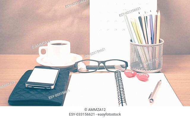 office desk : coffee with phone,wallet,calendar,color pencil box,notepad,heart on wood background vintage style