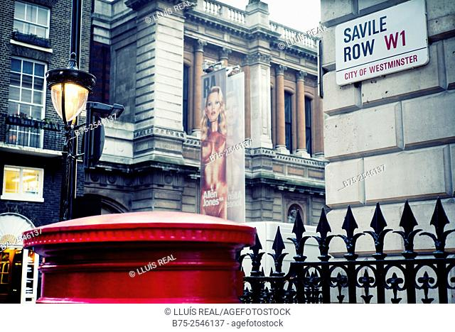 Sight of the plate of the street Savile Row W1, City of Westminster, with a fence of the building, lamp post on the background and a red mail box in foreground