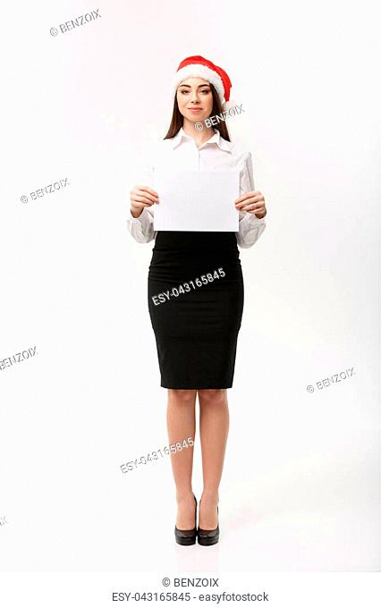 Business Concept - Beautiful young confident business woman with santa hat holding white blank paper celebrate for Christmas