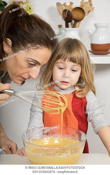 three years old child and woman, in teamwork, making and cooking a sponge cake at kitchen home, looking at metal whisk with whipped cream with egg