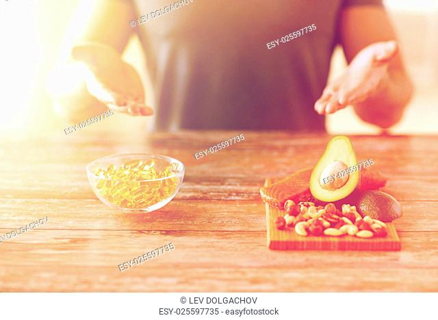healthy eating, diet and people concept - close up of male hands showing food rich in protein on cutting board on table
