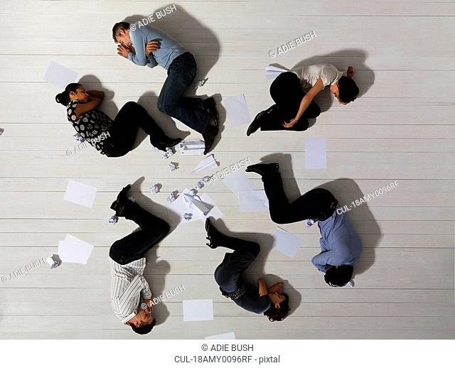 Business men and women asleep on floor