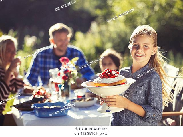 Portrait smiling girl serving strawberry cake to family at sunny garden party patio table