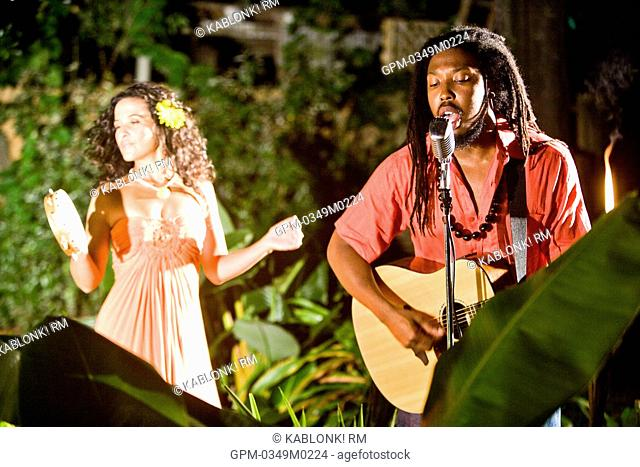 Young Jamaican man singing and playing guitar with Hispanic woman on tambourine on tropical island