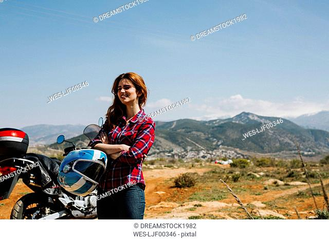 Happy redheaded woman with motorbike enjoying view, Andalusia, Spain