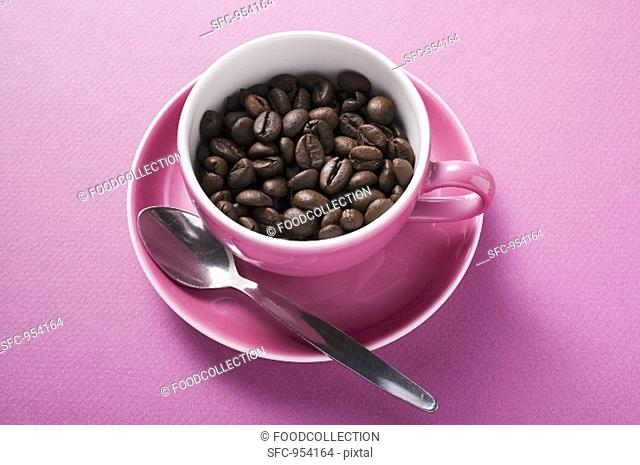 Coffee beans in pink coffee cup with spoon in saucer