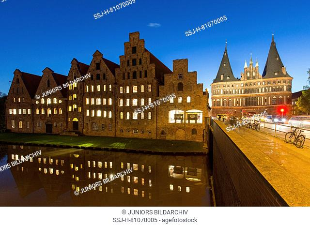 Historic salt storehouses (Salzspeicher) and the Holsten Gate on the river Trave in Luebeck, Schleswig-Holstein, Germany at night