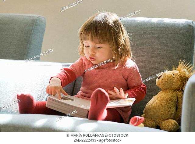 18 months old baby girl looking and pointing at inside a book
