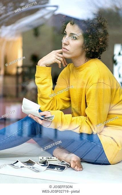 Serious woman sitting behind window at home holding photos