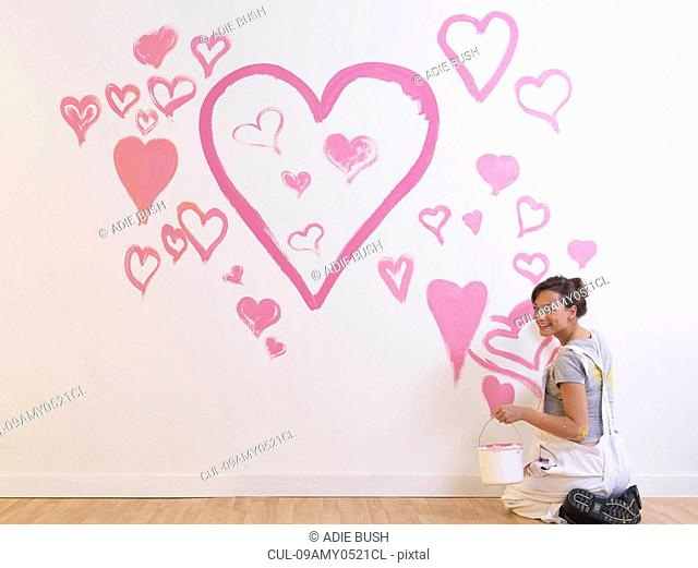 Girl paints pink hearts