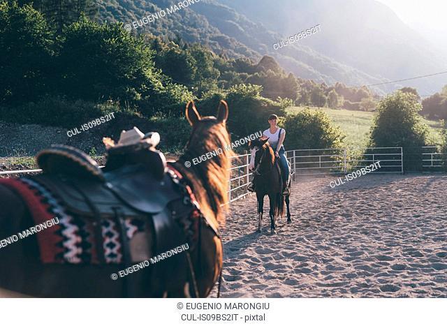 Young woman on horseback in rural equestrian arena, Primaluna, Trentino-Alto Adige, Italy