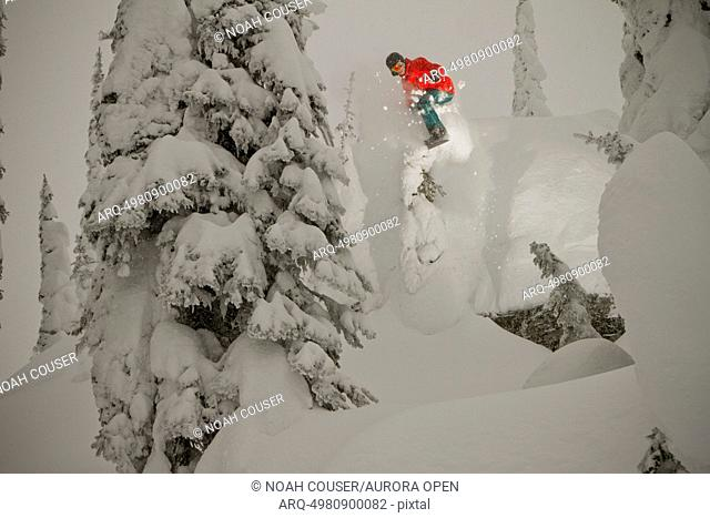 A snowboarder drops a small cliff on a cloudy winter day