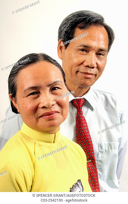 A Vietnamese American husband and wife pose in Westminster, CA. Note wife in traditional dress. . MODEL RELEASE