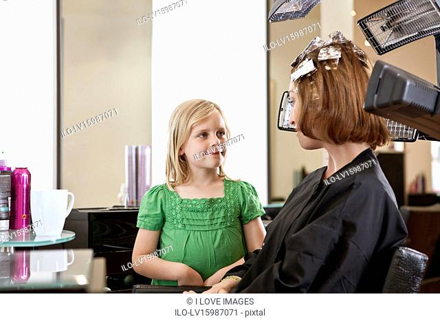 A young girl waiting in a hairdressing salon whilst her mother has her hair coloured