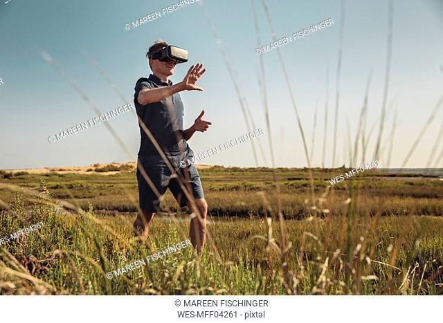 Mature man wearing VR glasses walking trough grass