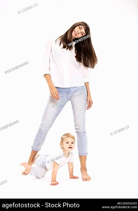 Mother standing while daughter crawling against white background in studio