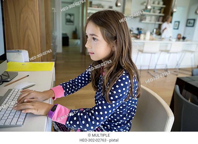 Girl in pajamas using computer at desk