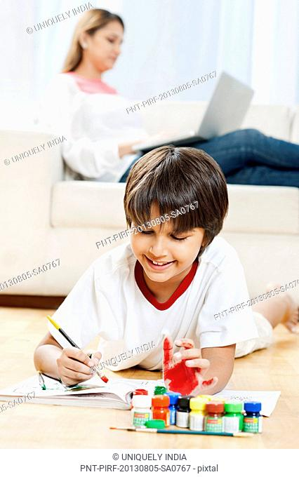 Boy making a painting with his mother using laptop in the background