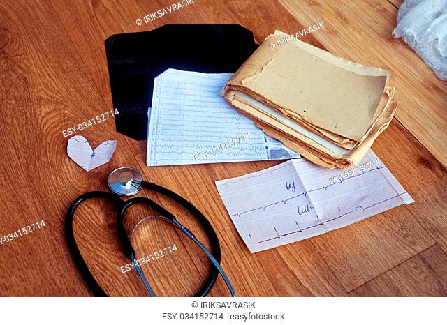Medical history, ECG, X-rays, analyzes and stethoscope on the wooden background