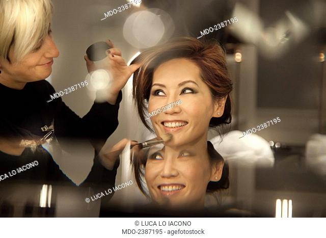 Close-up of the beautiful Chinese Canadian actress and soprano Lu Ye being prepared by a make-up artist. Photo shooting at the Hotel J. K