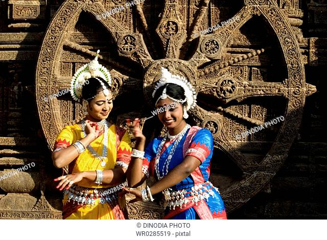 Odissi dancers enact scene from traditional ballet in front of iconic sculpture of Sun-god wheel at world heritage Sun temple complex , Konarak , Orissa
