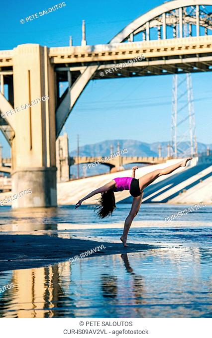 Side view of dancer, leg raised, bending over backwards in front of bridge, Los Angeles, California, USA