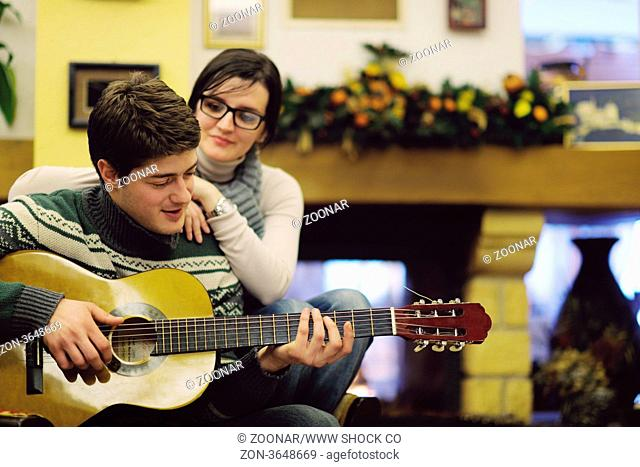 c86dc46e19a20 happy Young romantic couple and relaxing sofa in front of fireplace at  winter season in home. The beautiful girl in a cowboy s hat and acoustic  guitar