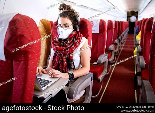 Young woman wearing a face mask while she works on an almost empty airplane due to the travel concerns and restrictions caused by the Covid-19 pandemic