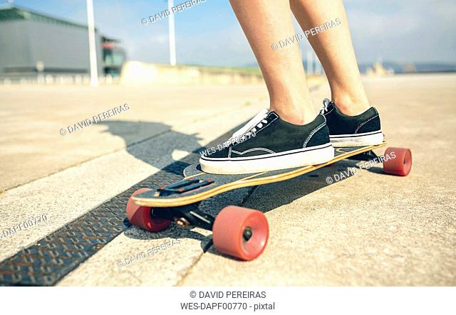 Feet of young woman on longboard, close-up