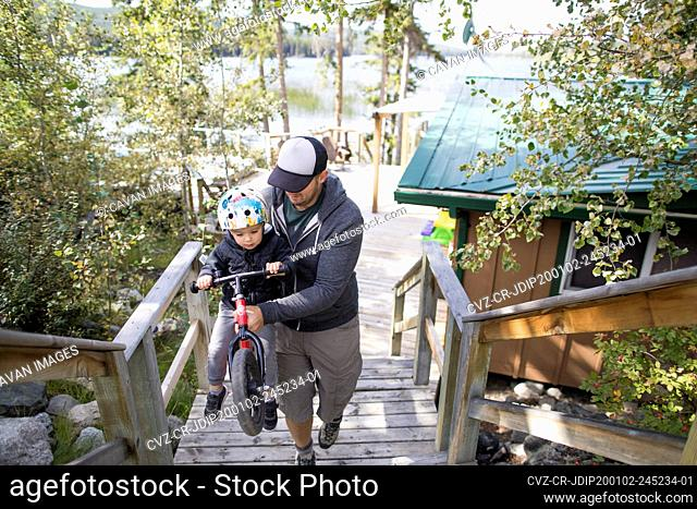 Father carries son on bike upstairs during vacation