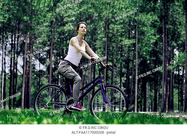 Woman sitting on bicycle in forest