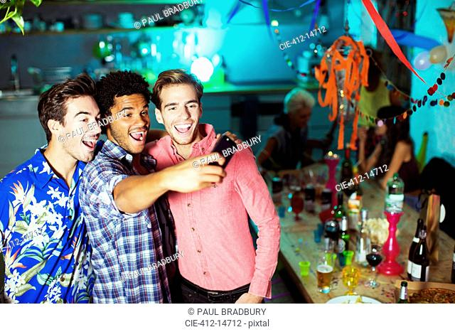 Men taking self-portraits with camera phone at party