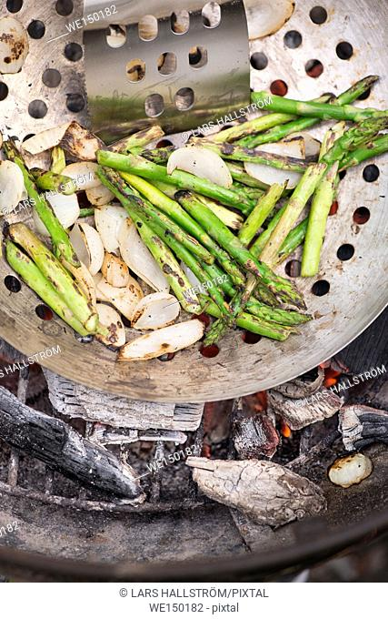 Grilling green asparagus in pan over hot charcoal. Cooking outdoors in summer. Vegetarian barbecue with vegetables